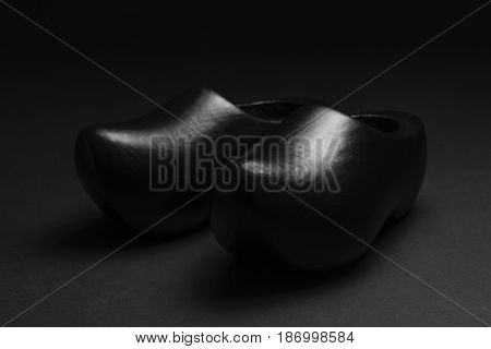 Two traditional Dutch black wooden shoes in a low key recording