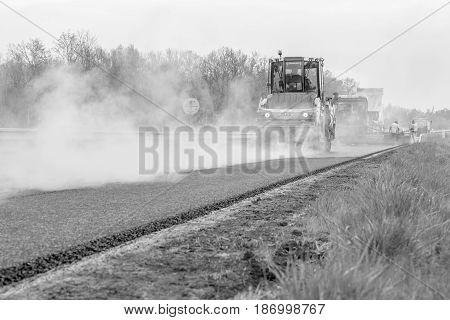 CZECH REPUBLIC, PLZEN, 7 MAY, 2016:Asphalt spreading machine and vibration roller  at pavement road works.Black and white photo.