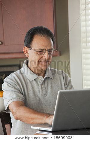 Hispanic man using laptop in kitchen