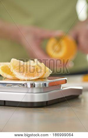 Senior woman weighing orange on scale