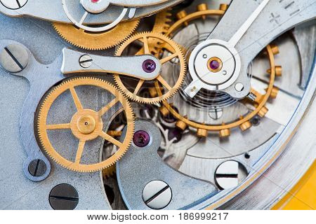 Clock transmission macro view. Stopwatch chronometer mechanism cogs gears wheels connection concept. Shallow depth of field, selective focus.