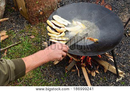 Preparing food outdoors roaster full of Porcini wild mushrooms fried in deep oil