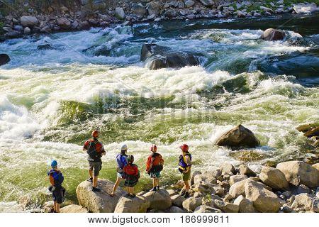 Caucasian family standing near rapids in river