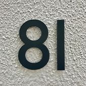 Number 81 painted black metal house address sign screwed into painted white wall textured background poster