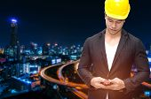 smart construction manager in suite with walkie-talkie or two way radio in hand and yellow safety helmet with blurred night city background industrial technology concept. poster