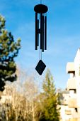 Silhouette of feng shui chimes with nature in the background with a clear blue sky and defocused tree in the background on a sunny day poster