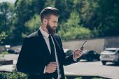 Young stylish bearded business man in a classy suit is browsing his pda on the street at the sunny day. He is ordering a cab by pda poster