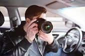 The man in the car reviews the photos on the camera. Spy, paparazzi, journalist, photographer. poster