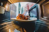 Man putting grilled chicken into microwave oven. inside view poster