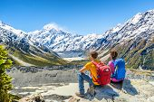 Backpackers couple hiking looking at Mt Cook view on mountains tramping in New Zealand. People hikers relaxing during hike in alps of south island. poster
