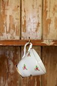 tea cup hanging on a hook in old wooden cupboard, shallow DOF poster