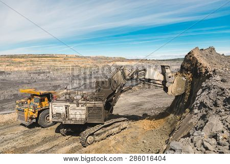 White Big Excavator In The Coal Mine, Loads The Breed, With The Bright Sun And Nice Blue Sky In The
