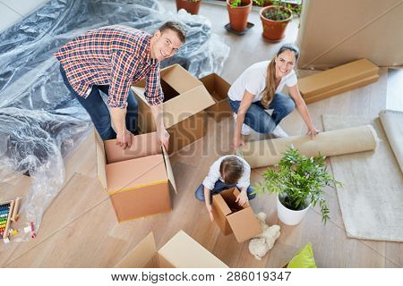 Family and child packing moving boxes when moving to new apartment or house