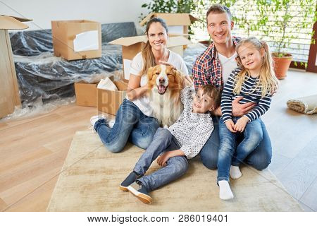 Happy family with two kids and dog in new home as a home