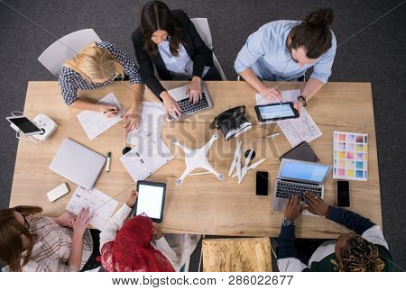 multiethnic startup business team discussing new business plan,working on laptop and tablet computer while learning about drone technology for future business ventures top view
