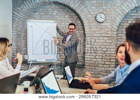 Businessman At Whiteboard Giving Presentation In Boardroom