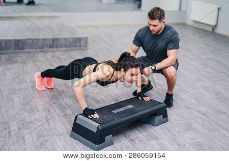 Attractive Woman Doing Push-up With The Help Of A Personal Instructor Isolated On Wooden Floor Backg