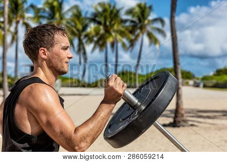 Outdoor calisthenics gym park male athlete working out on T-bar outside in summer. Man workout strength training arms biceps muscles with heavy weights.