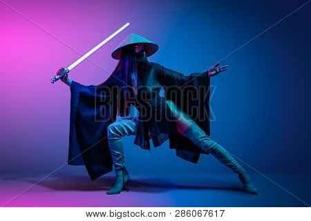 Concept on cosmic cosplay. Сontemporary portrait a young athletic woman in traditional Japanese black kimono, an Asian hat and highboots is holding a lightsaber and posing on neon blue-pink background poster