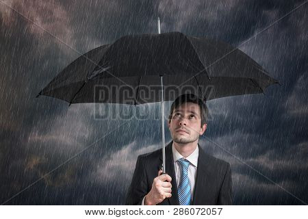 Pessimistic Businessman With Black Umbrella In Storm.