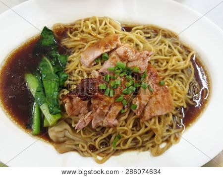Top view of egg noodle with shrimp wontons and roasted duck topped with sliced scallion on white plat poster