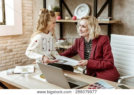 Smiling Contented Blonde Mother Having Fun With Her Positive Daughter At Work