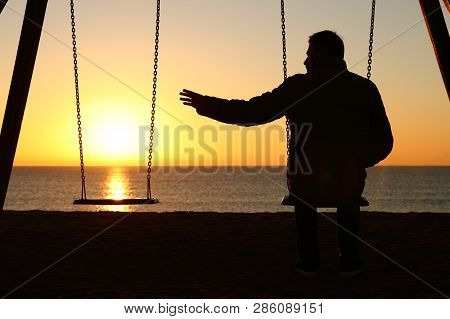 Back View Backlighting Silhouette Of A Man Sitting On Swing Alone Missing Her Partner At Sunset On T