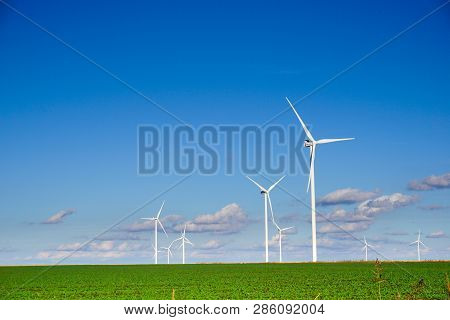 Wind Power Plant Consisting Of Several Wind Turbines Standing In A Field Against A Sky