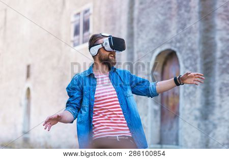 Man walking in the street in augmented reality headset. Virtual reality and futuristic technology concept.