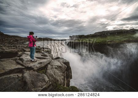 Woman Traveler At Amazing Iceland Landscape Of Dettifoss Waterfall In Northeast Iceland. Dettifoss I