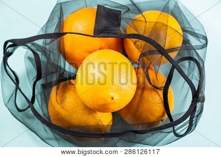 Top View Of Oranges In A Reusable String Bag. Sustainable Eco Packaging Concept: Shopping For Grocer