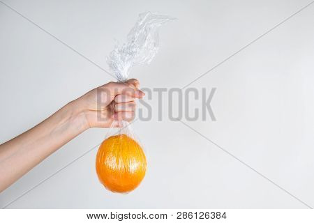 Excessive Plastic Use Concept: Orange In Plastic Wrap Held In A Hand. Unreasonably Over-packaged Foo