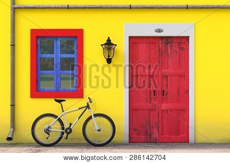 Bicycle Parked In Front Of Retro Vintage European House Building With Red Door, Blue Window And Yell
