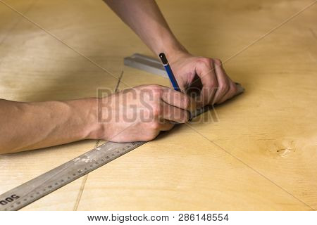 Man's hands marking measurement on plywood board with a pencil and speed square ruler. poster