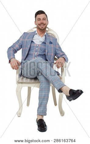 A man in a suit is sitting on an expensive chair. Front view of a guy in stylish clothes on a chair. Isolated on white background. A rich, confident man smiling looking into the frame.