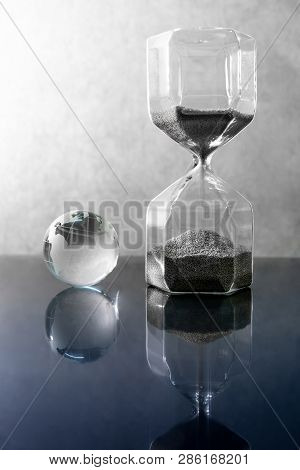 Reflection Of Silver Sand Running Through The Shape Of Hourglass With World Globe Crystal Glass On T