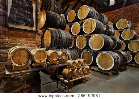 Rows Of Alcoholic Drums In Stock. Distillery. Cognac, Whiskey, Wine, Brandy. Alcohol In Barrels