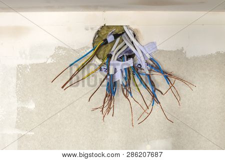 Electrical exposed connected wires protruding from socket on white wall. Electrical wiring installation. Finishing works in renovated apartment. poster