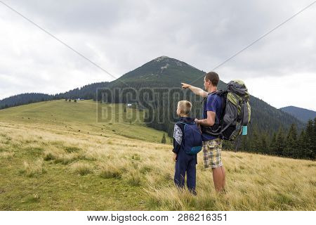 Father And Son With Backpacks Hiking Together In Summer Mountains. Back View Of Dad And Child Holdin