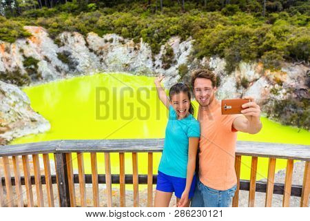 New Zealand tourist attraction couple tourists taking selfie travel destination, Waiotapu. Active geothermal green pond, Rotorua, north island, Wai-O-Tapu, New Zealand.