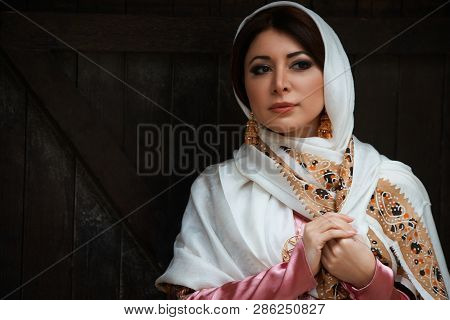 Young Azeri Woman In Traditional Azerbaijani Dress Standing At The Wooden Door