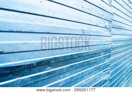 Industrial metallic background. Corrugated zinc metal texture, metal fence closeup view. Metal background
