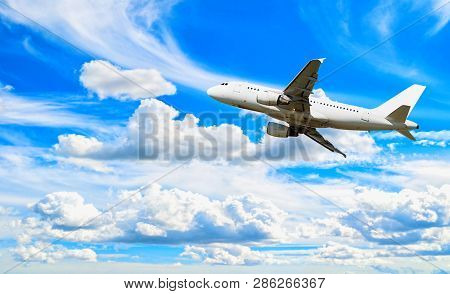 Airplane flying in the sky - travel background with white airplane. Commercial airplane, airplane travel concept. Airplane with blank livery, airplane in the flight. Travel landscape with flying airplane