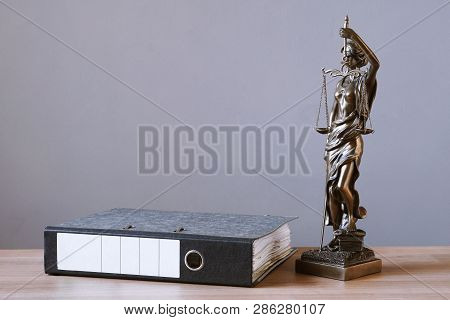 Lady Justice Or Justitia Statue And File Folder On Desk - Law And Legal Concept - Background With Co