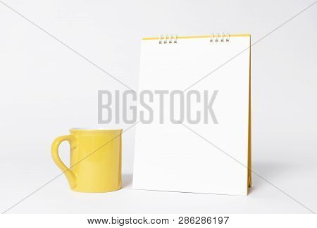 Blank Paper Spiral Calendar And Yellow Cup For Mockup Template Advertising And Branding Background.