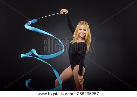 Young Beautiful White Caucasian Girl Gymnast Doing Gymnastic Exercise With Blue Ribbon On Black Back