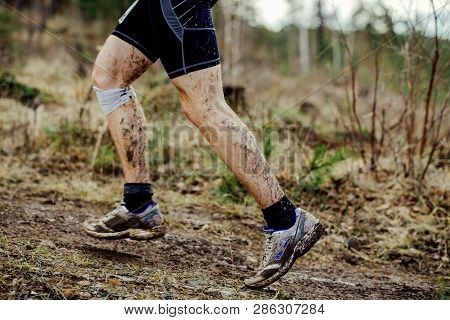 Dirty Feet Runner Running Uphill Trail. Injured Knee In Bandage