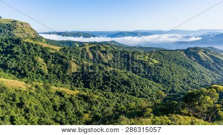 Scenic thousand hills valleys and zulu homes in rugged bush terrain with morning cloud mist rising over the landscape. poster
