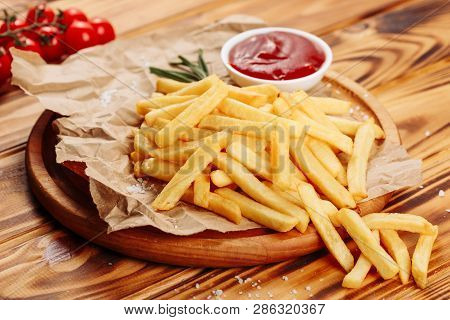 French Fries Potato Snack Ketchup Sauce Closeup. Golden Fry Chip Fast Food On Wooden Rustic Board. C