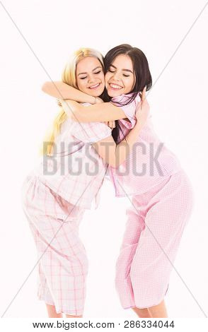 Blonde And Brunette On Smiling Faces In Clothes For Sleep Looks Cute And Friendly. Girls Hugging Tig